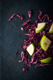 Salad of red cabbage and apples on the dark stone Royalty Free Stock Photography