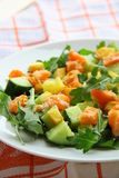 Salad with red fish. Salad with cucumbers, red fish and potatoes on a plate royalty free stock photo