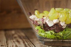 Salad from red and green lettuce leaves with chicken and grapes Royalty Free Stock Photo