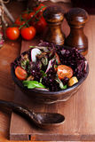 Salad with red lettuce and radish glass bowl wooden table in still life Stock Image