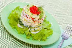 Salad with red salmon caviar. Food - plate with snack with crabbing salad and red salmon caviar on green leaf of lettuce Royalty Free Stock Photo