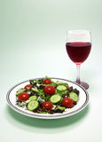 Salad and Red Wine. A summer salad featuring spring mix greens, cherry tomatoes, feta cheese, persian cucumbers, dried cranberries, and a glass of red wine Stock Images