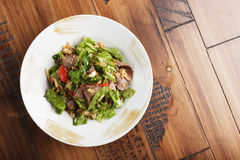Salad with roast beef. In a white plate. Brown wooden background Royalty Free Stock Photography