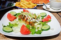Salad with roast veg, Gozo. Mixed salad topped with roast vegetables and shredded leek with pizza and chips to the rear on a wooden table within the citadel Stock Image