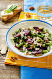 Salad with roasted beets, green beans, walnuts and goat cheese. On a dark wood background. tinting. selective focus on the middle of the salad stock photo