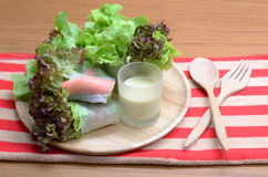 Salad roll vegetables and crab stick with salad dressing. In wooden plate, folk and spoon stock photos