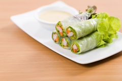 Salad rolls and cream sauce on white plate and wooden table. Salad rolls on white plate Stock Image