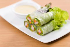 Salad rolls and cream sauce on white plate and wooden table. Salad rolls. white dish. wooden table Royalty Free Stock Image