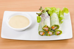 Salad rolls and cream sauce on white plate and wooden table. Salad rolls on white dish and wooden table Stock Photography