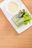 Salad rolls and cream sauce on white plate and wooden table. Salad rolls and space Stock Images
