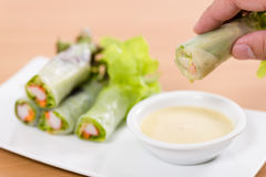 Salad rolls on hand. White plate. Wooden table. Hand holding salad roll Royalty Free Stock Photo