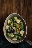 Healthy Salad Romanesco in bowl. Salad Romanesco cauliflower buds closeup, in bowl on wood background. Tasty salad with romanesco, quail eggs, corn grain mais royalty free stock photography