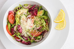 Salad of romano, frisse, and radiccho leafs with tomato, onion, and avocado Stock Photo