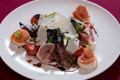 SALAD WITH RUCOLLA AND prosciutto parmesan. Parmesan WITH prosciutto WITH salmon WITH RUCOLLA WITH RED vegetables WITH liver WITH pork and chicken liver WITH royalty free stock images