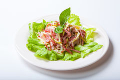 Salad from a salami, ham and cheese on a white plate Stock Photo