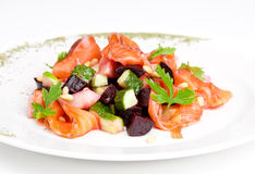 Salad with salmon, beet, potatoe, cucumber and. Cedrine nuts on the plate Royalty Free Stock Images