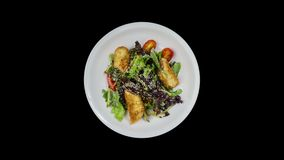 Salad with salmon in breadcrumbs with lettuce and sesame seeds. Isolated on the black background. stock video