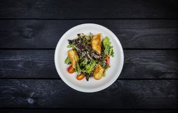 Salad with salmon in breadcrumbs with lettuce and sesame seeds. stock image