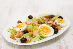 Salad with salmon, eggs and olives on white dish Stock Photo