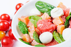 Salad with Salmon, Grapefruit, Spinach and Mozzarella with Cherr. Y on a White background Royalty Free Stock Images