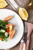Salad with salmon grilled in sesame seeds, cherry tomatoes and quail egg on wooden table. Salad with salmon grilled in sesame seeds, cherry tomatoes and quail Royalty Free Stock Image