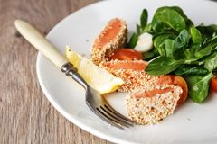 Salad with salmon grilled in sesame seeds, cherry tomatoes and quail egg on wooden table. Salad with salmon grilled in sesame seeds, cherry tomatoes and quail Stock Images