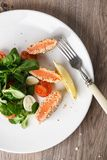 Salad with salmon grilled in sesame seeds, cherry tomatoes and quail egg on wooden table. Salad with salmon grilled in sesame seeds, cherry tomatoes and quail Stock Photography