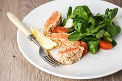 Salad with salmon grilled in sesame seeds, cherry tomatoes and quail egg on wooden table. Salad with salmon grilled in sesame seeds, cherry tomatoes and quail Stock Image
