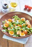 Salad with salmon, quail eggs, cherry tomatoes and red caviar Stock Image