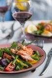 Salad with salmon and verdure in plate on table with blue chair Royalty Free Stock Image