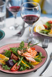 Salad with salmon and verdure in plate on table with blue chair Stock Images