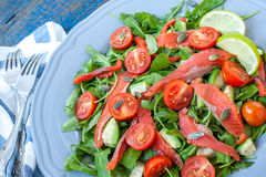 Salad with Salted salmon, herbs, tomatoes, avocado on a plate. Love for a healthy raw food concept Stock Image