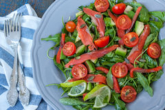 Salad with Salted salmon, herbs, tomatoes, avocado on a plate. Love for a healthy raw food concept Stock Photos