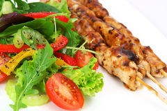 Salad and Satay. Delicious salad with chicken satay skewers. Focus on cherry tomato royalty free stock photo