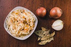Salad of sauerkraut and carrots with black pepper in a white plate and a few onions, laurel leaves and cumin seeds. On a wooden table royalty free stock image
