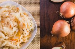 Salad of sauerkraut and carrots in a white plate and several onion bulbs on a wooden table stock photography