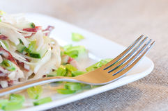 Salad with sausage, cucumber, cabbage and green peas Royalty Free Stock Images