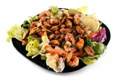 A salad with seafood on a black plate Royalty Free Stock Photo