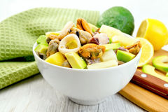 Salad with seafood and lemon in bowl on light board Royalty Free Stock Photo