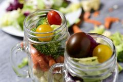 Salad served in some mason jars. Salad made with a mix of different lettuces, broccoli, green pepper, carrot and cherry tomatoes of different colors served in Royalty Free Stock Photography