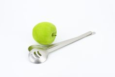 Salad servers and green apple Stock Images