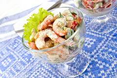 Salad with shrimp and avocado in glass on tablecloth. Salad with shrimp, avocado, tomato and mayonnaise, green salad in a glass goblet on a background of blue Royalty Free Stock Image