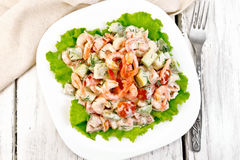 Salad with shrimp and avocado in plate on board top Stock Image