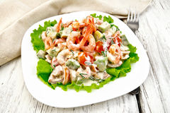 Salad with shrimp and avocado in white plate on light board Royalty Free Stock Image