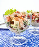 Salad with shrimp and tomatoes in glass on tablecloth. Salad with shrimp, avocado, tomatoes, green lettuce in a glass goblet, a plate against the background of a Royalty Free Stock Photos