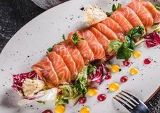 Salad of sliced salmon fillet with lettuce, cabbage and sauce in plate on dark grey background. Healthy food, clean eating. Dieting, closeup royalty free stock images