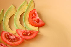 Salad Slices. Tomato and Avocado Slices on a yellow plate Royalty Free Stock Image