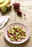 Salad of slices of various fruits and pomegranate seeds on a wooden background stock photo