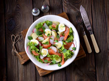 Salad from slightly salted salmon, boiled potatoes, quail eggs with cucumber and radish. Royalty Free Stock Images