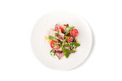 Salad with smoked ham and arugula in the white ceramic plate. On the white background top view Royalty Free Stock Images